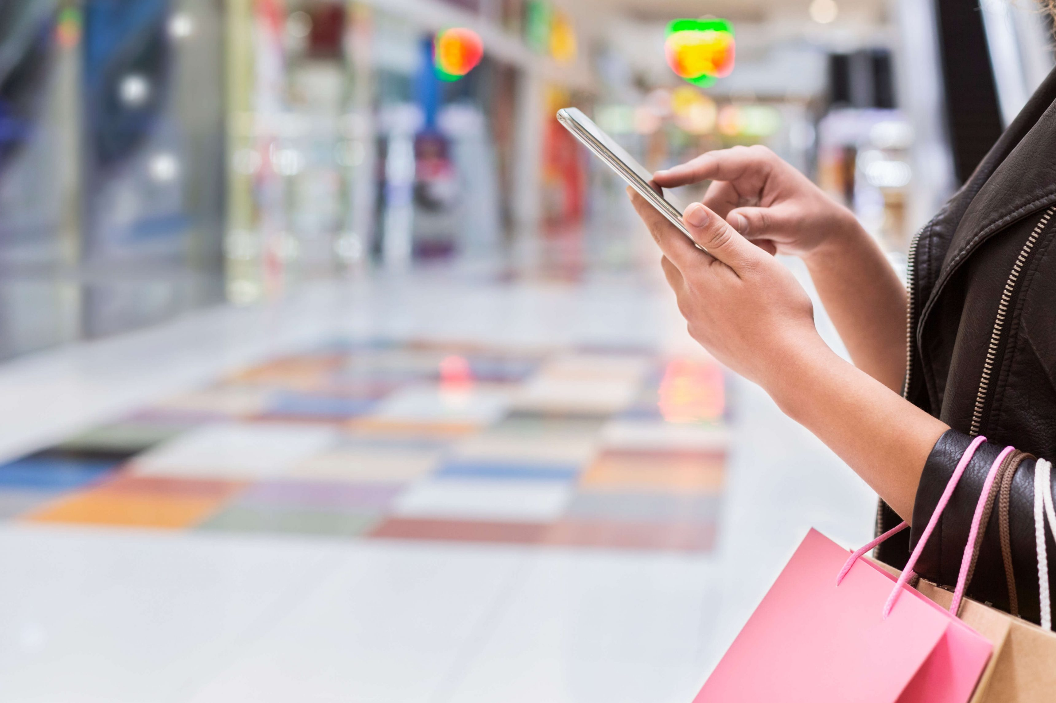 Mobile App with discount. Young african girl using cellphone to find shop in the big mall, panorama, free space